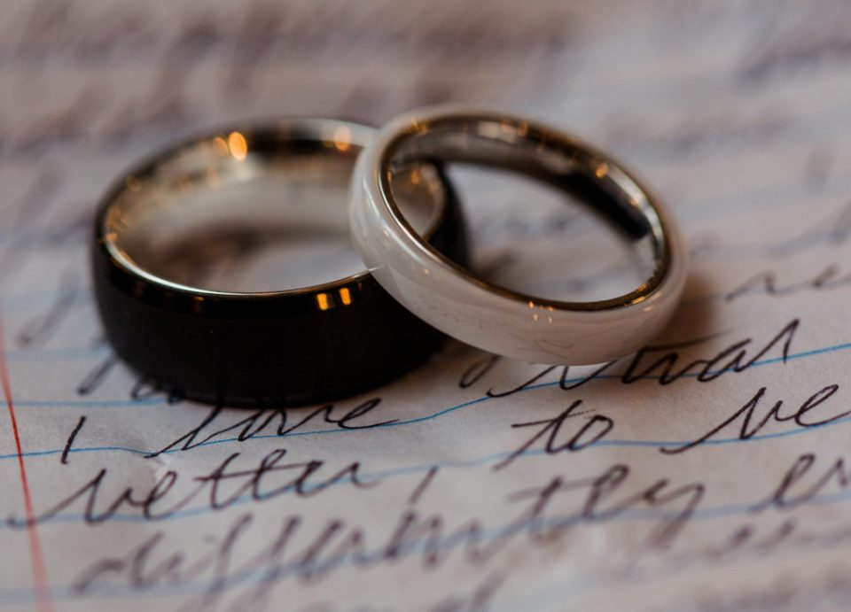 Wedding rings placed on top of handwritten vows