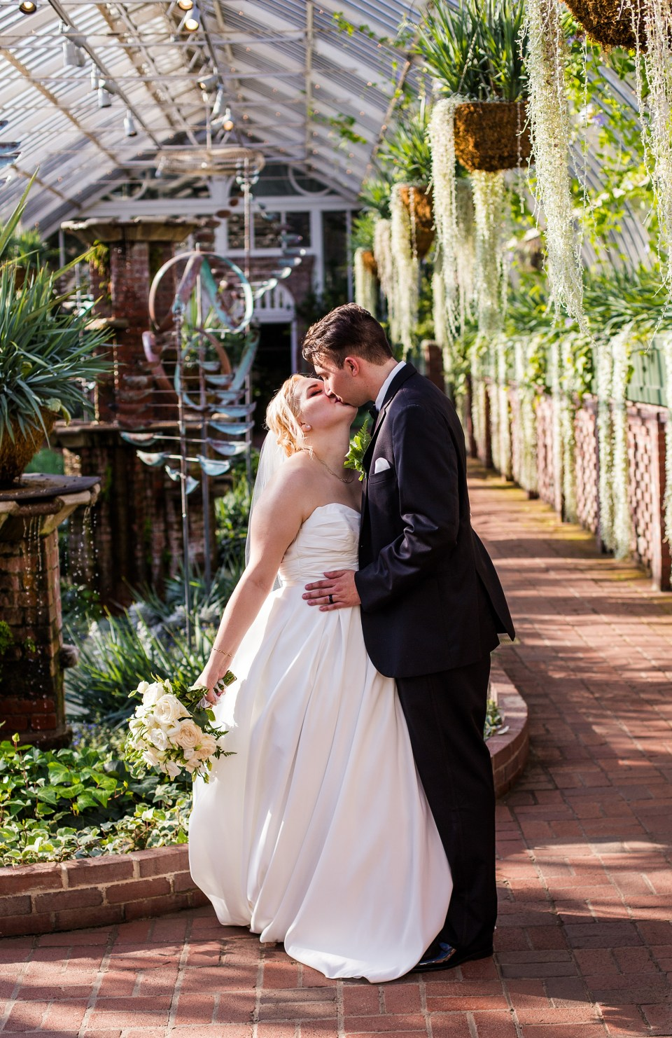 color image of Alexsys and Jon kissing in Phipps conservatory on their wedding day