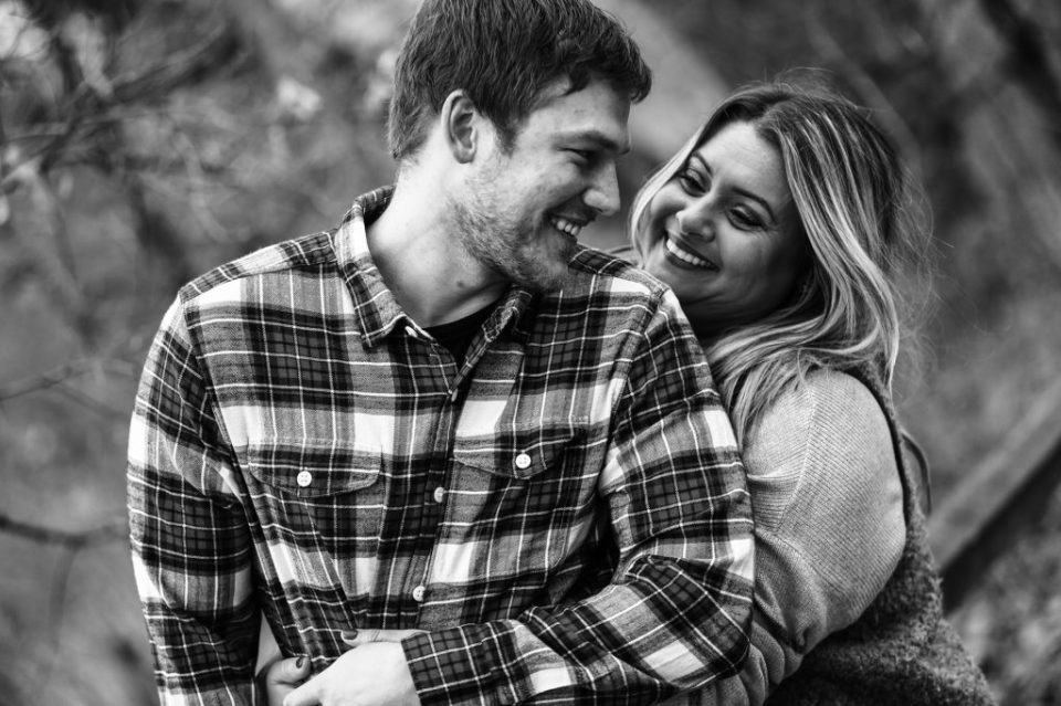 Woman sneaks up on her fiance during fall engagement photos in Frontier Park
