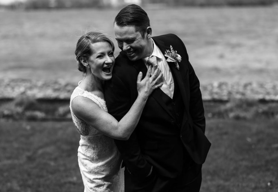 Bride and groom laugh together after their Presque Isle beach wedding