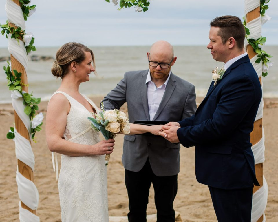 Groom holds bride's hand during Presque Isle beach wedding