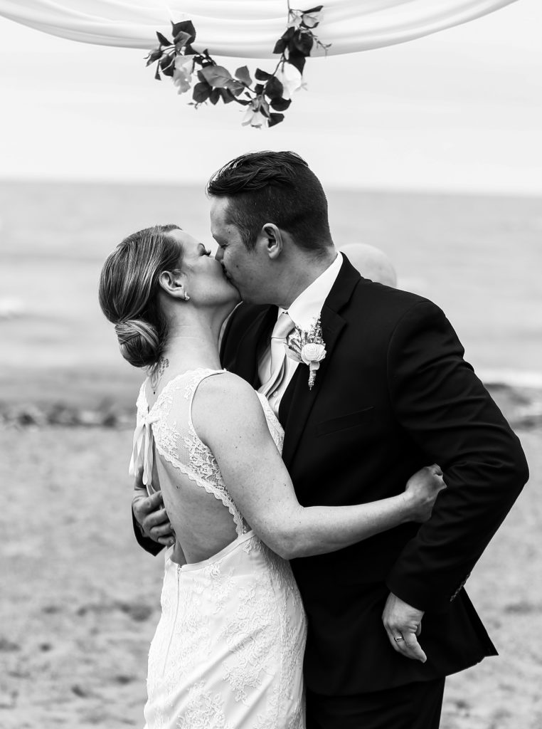 Bride and groom share first kiss at Presque Isle beach wedding ceremony