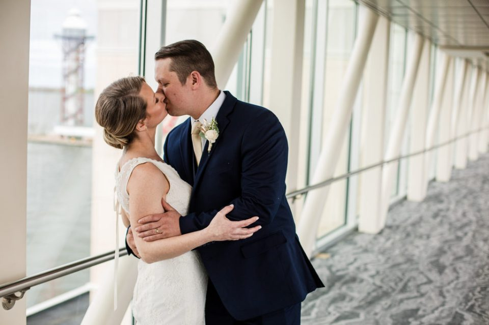Bride and groom kiss on the skybridge at the Sheraton Erie Bayfront Hotel