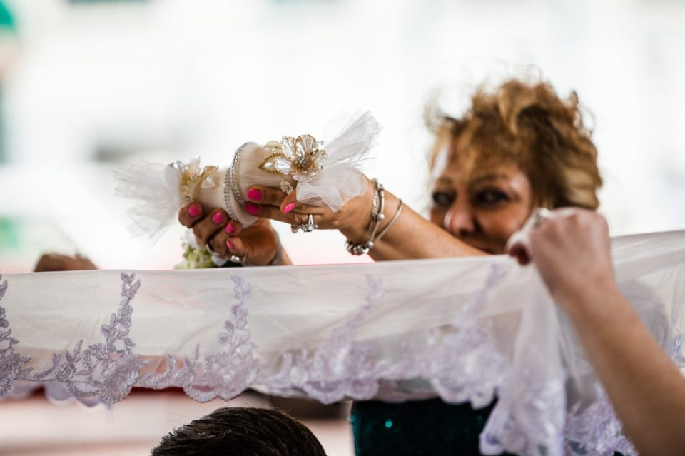 Woman sprinkles sugar over a cloth for Persian sugar ceremony at at Pittsburgh wedding