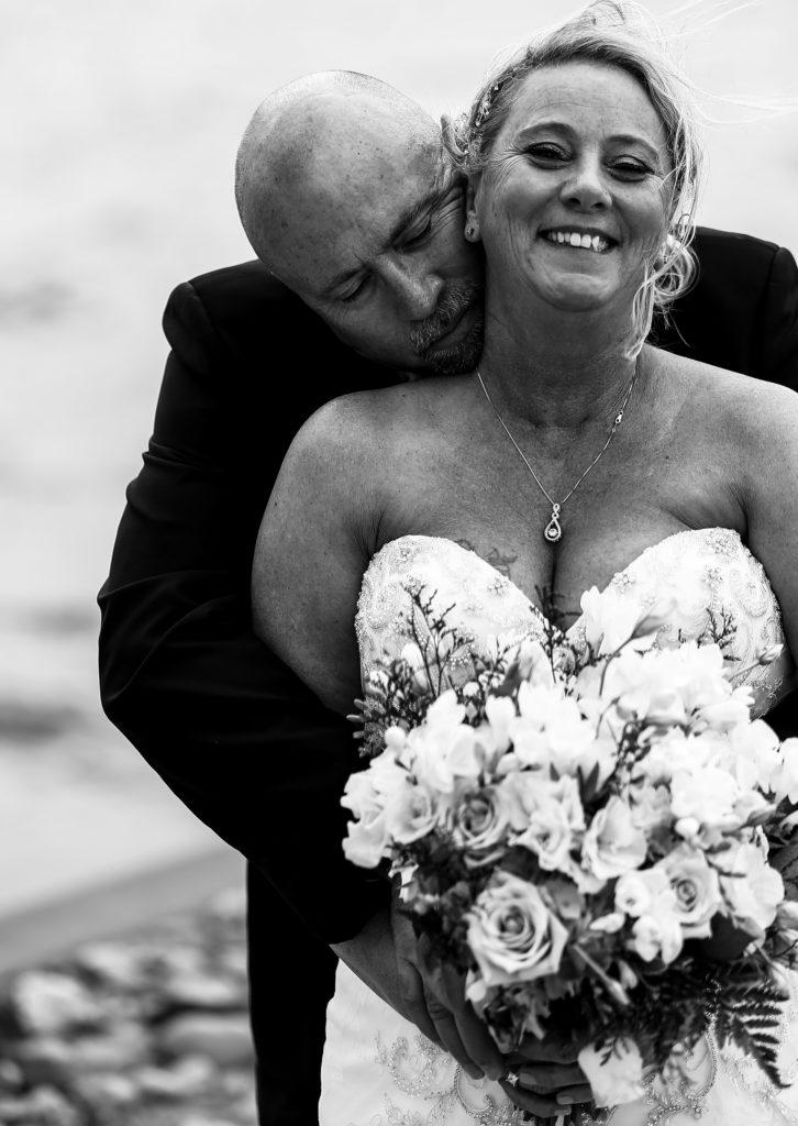 Groom hugs laughing bride outside Sheraton Erie Bayfront Hotel