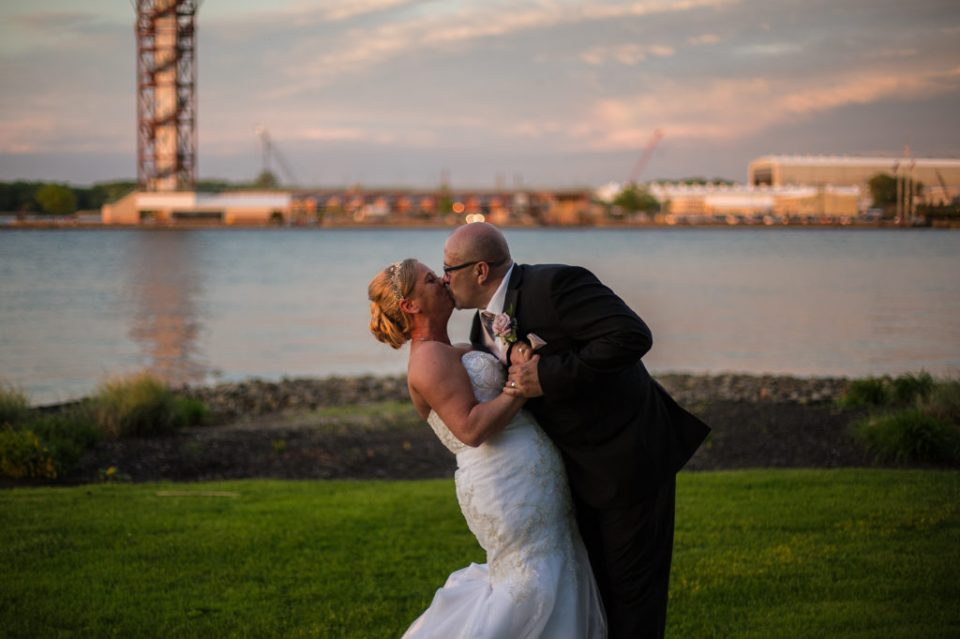 Bride and groom kiss at sunset outside the Sheraton Erie Bayfront Hotel