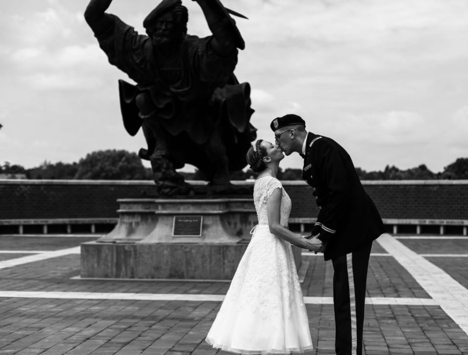 Bride and groom hold hands and kiss in front of Angus statue at their wedding at Edinboro University
