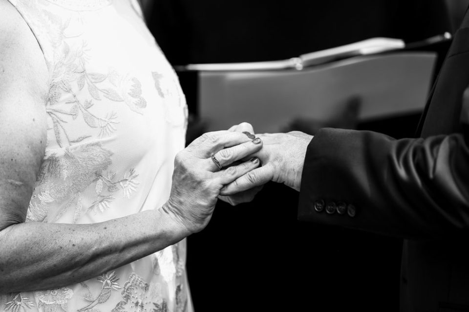 Couple exchanges rings during wedding at the Schoolhouse
