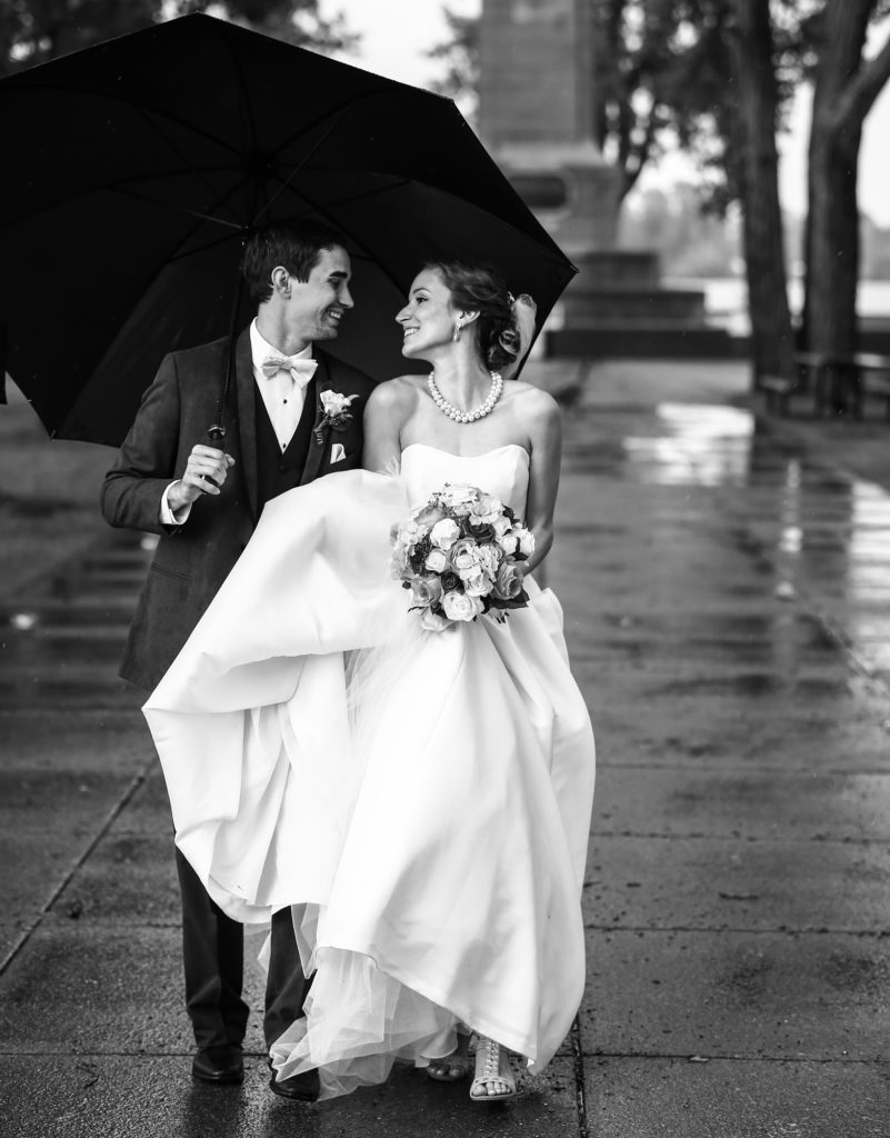 Bride and groom walking under umbrella at Perry Monument on Presque Isle State Park