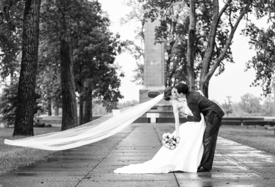 Bride and groom kiss while veil blows in the wind at Perry Monument on Presque Isle State Park