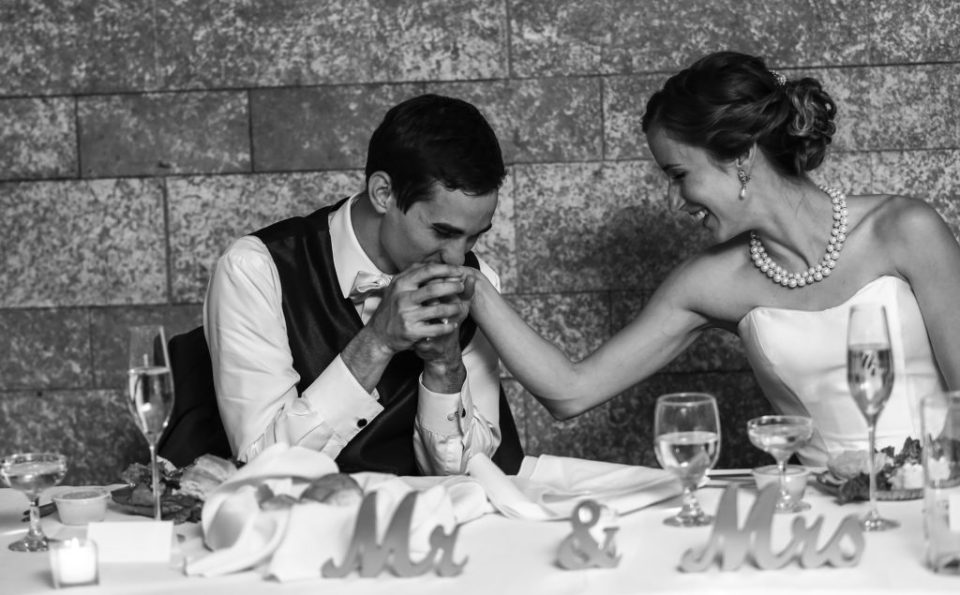 Groom kisses bride's hand during Masonic Temple wedding reception