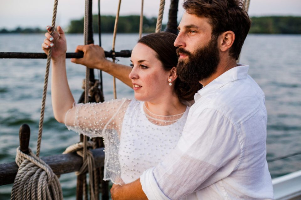 Bride and groom admire the horizon from the deck of the Lettie G Howard