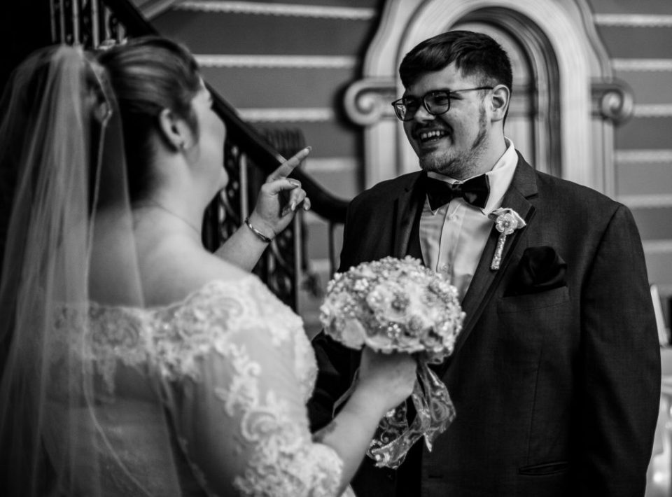 Groom smiles during first look portraits at a summer Warner Theatre wedding