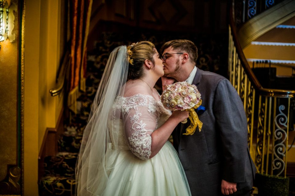 Bride and groom kiss during first look at summer Warner Theatre wedding