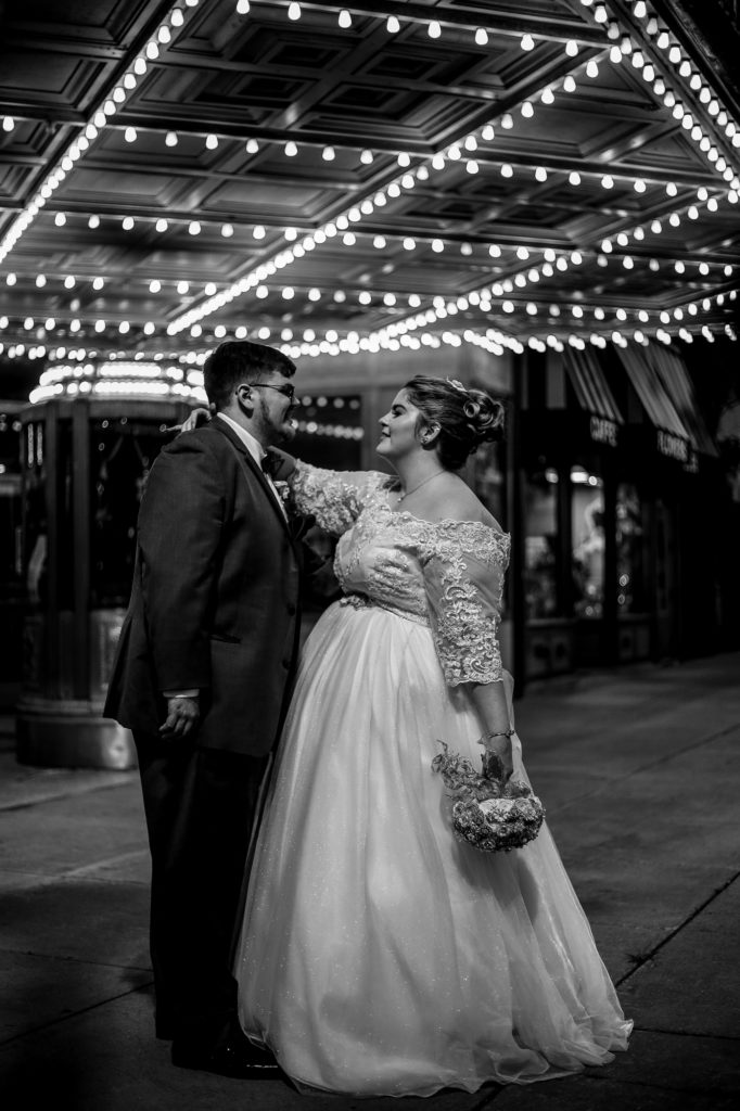 Bride and groom standing under the marquee at the Warner Theatre