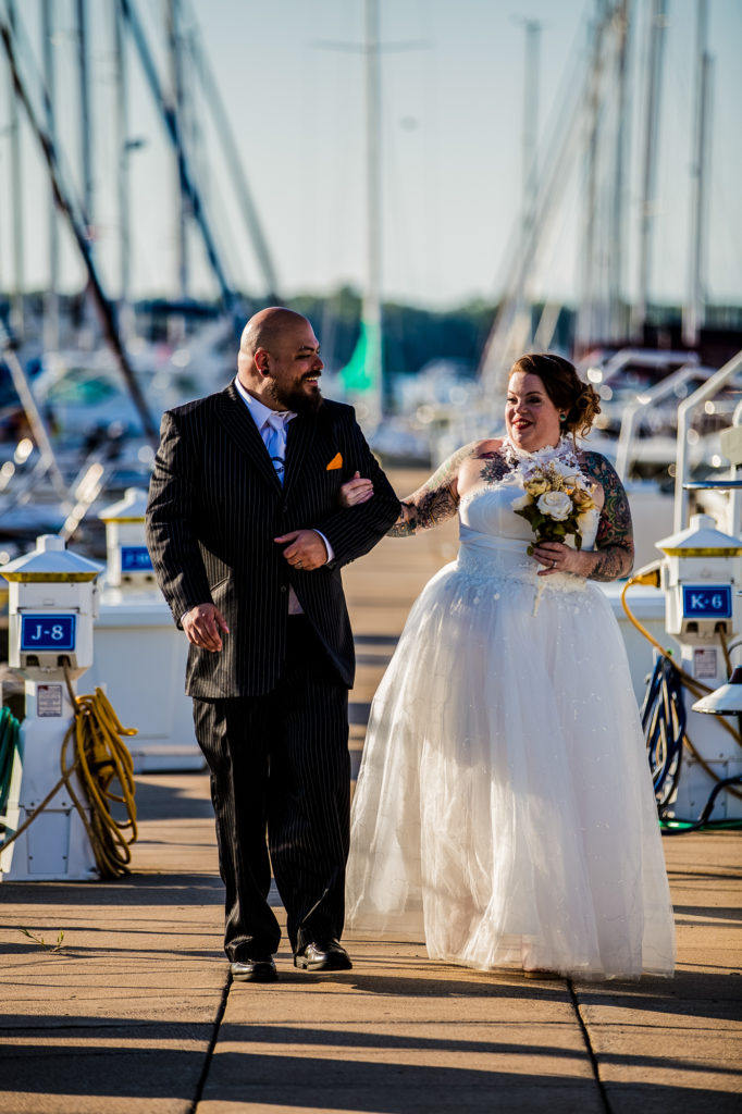 Bride and groom walking along a dock at the Erie Yacht Club