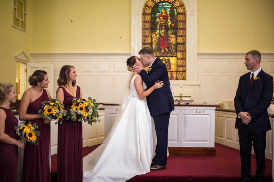 Bride and groom kiss at the end of their Emmanuel Presbyterian church wedding