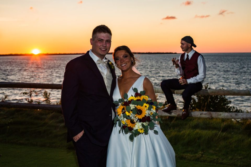 Bride and groom pose together at sunset at Lawrence Park Golf Club