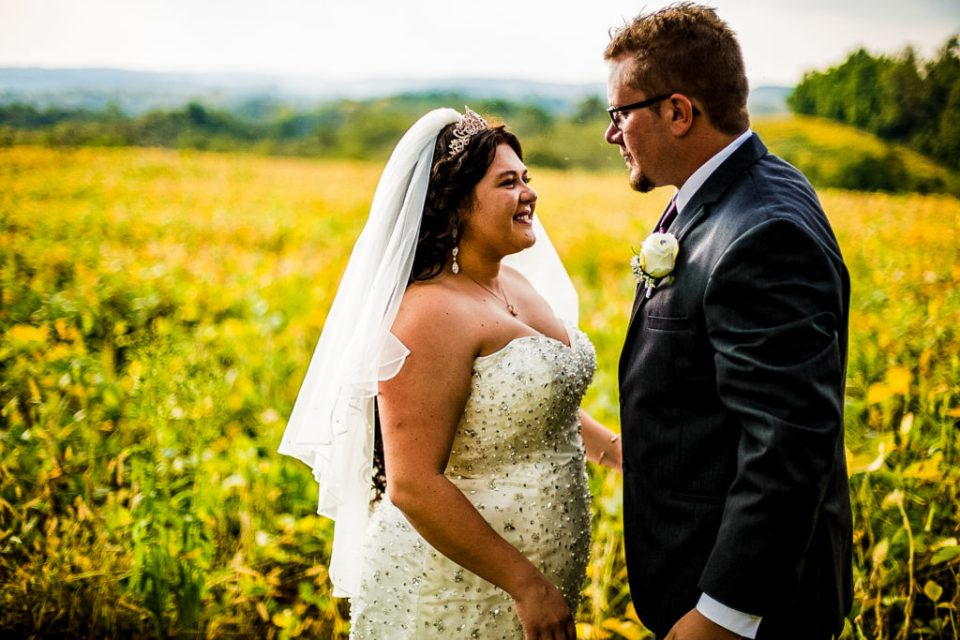 Bride and groom smiling in a field for a rustic Connellsville wedding