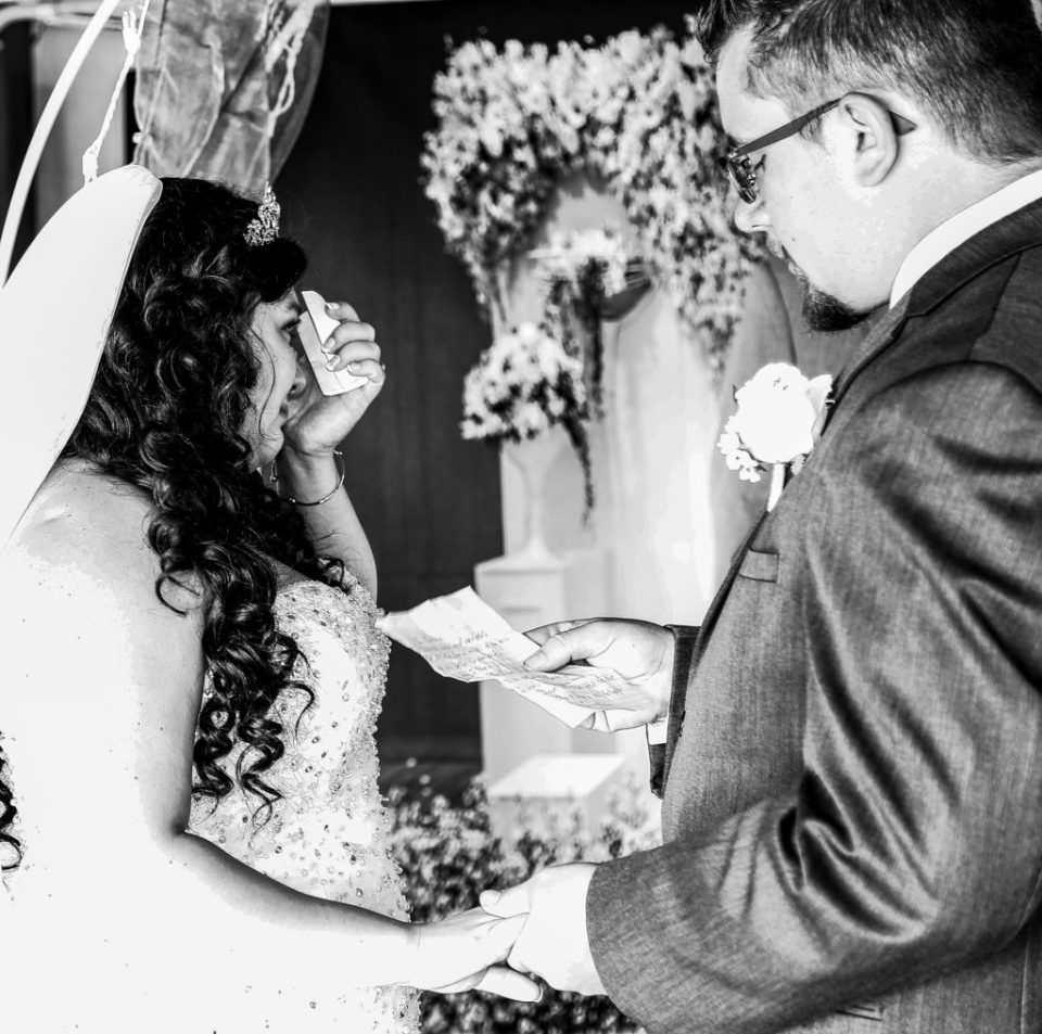 Bride wipes away a tear as groom reads his vows