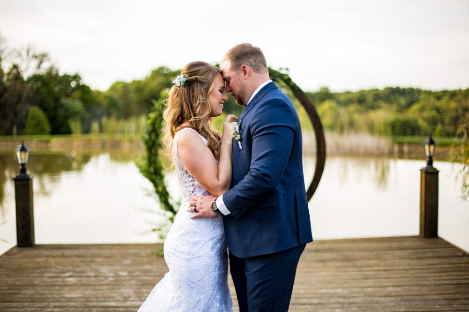 Bride and groom stand with foreheads together on the dock of Rustic Acres Farm
