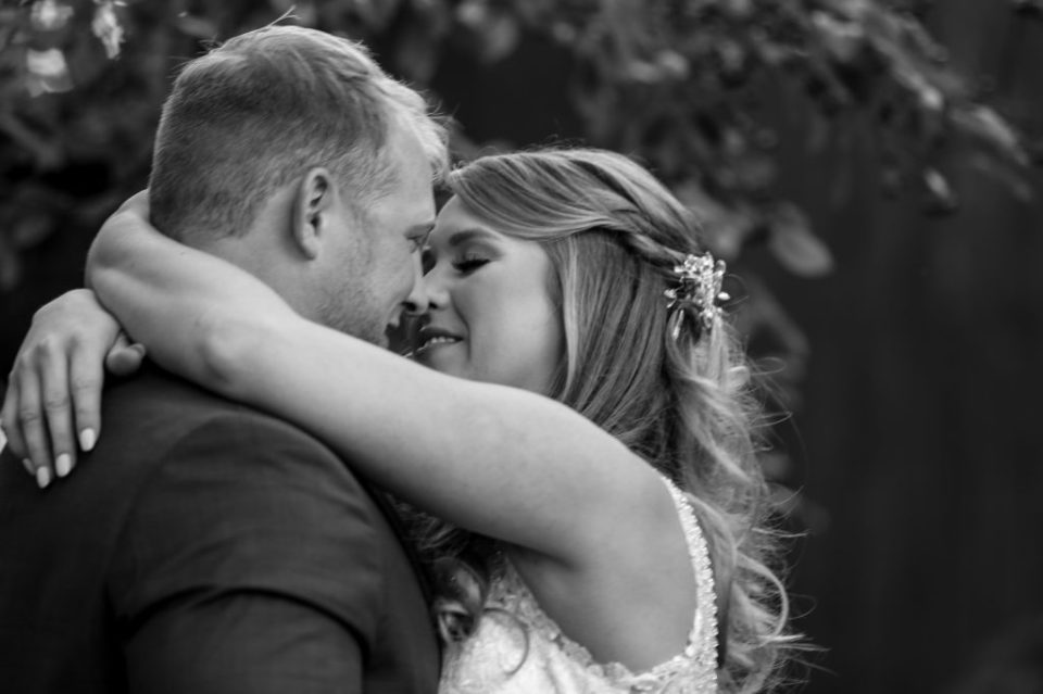 Bride embraces groom for a kiss at Rustic Acres wedding