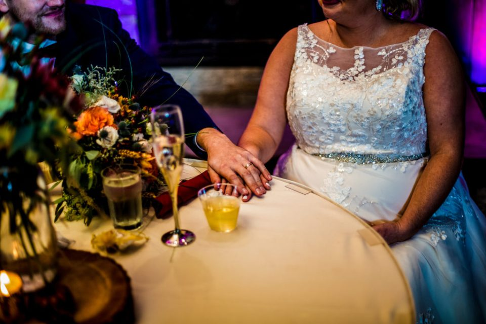 Groom puts his hand on top of bride's hand during wedding reception at Majestic Woods