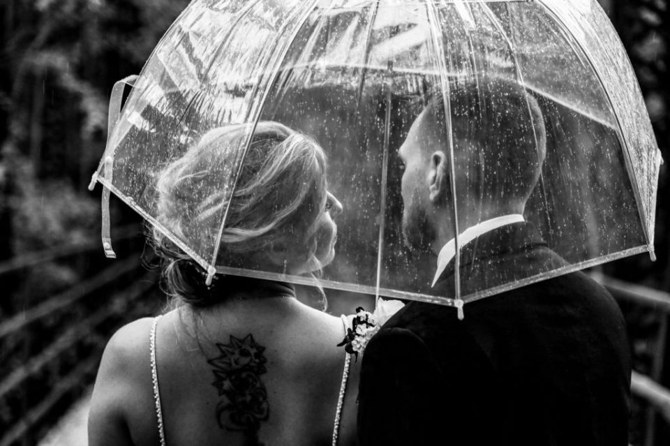 Bride and groom standing under an umbrella in the rain