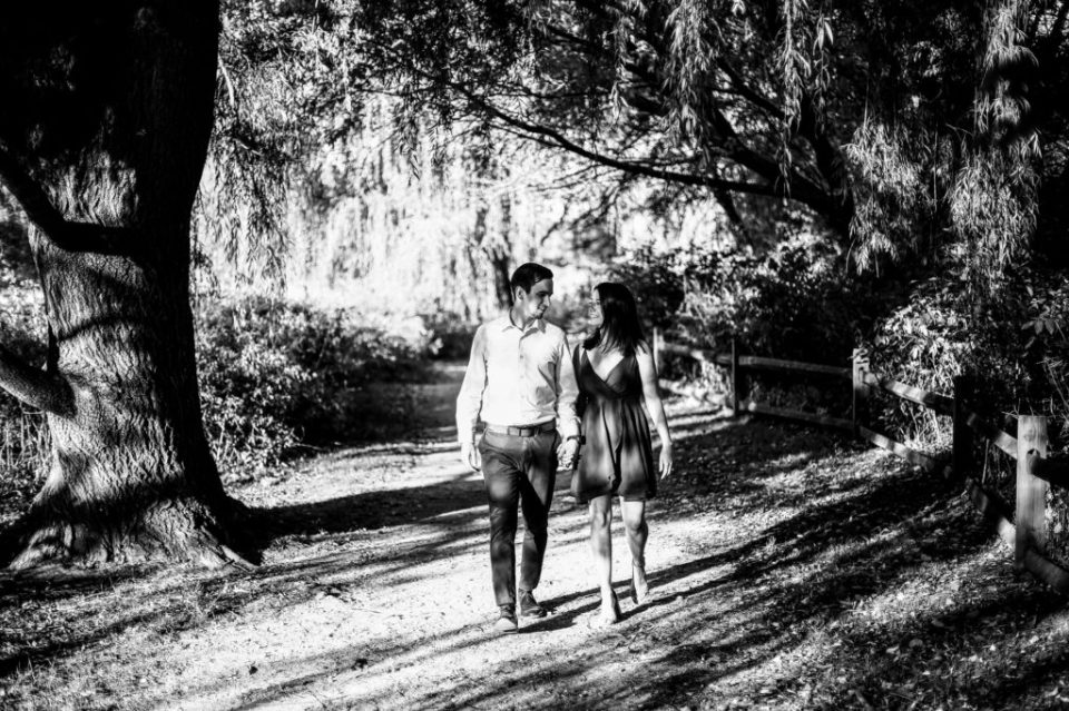 Engaged couple walk along a path engagement photos at Frontier Park in Erie, PA