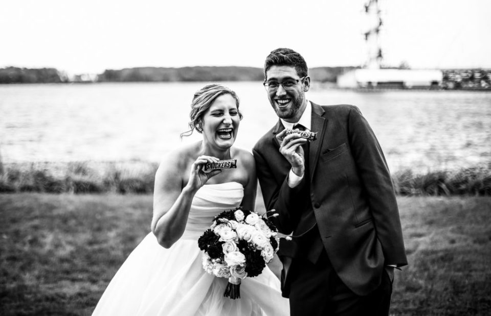 Bride and groom laughing while holding a snickers candy bar