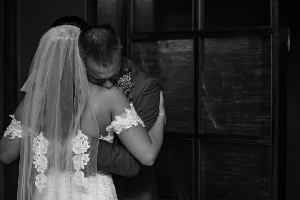 Man hugs his daughter during first look at downtown Erie wedding