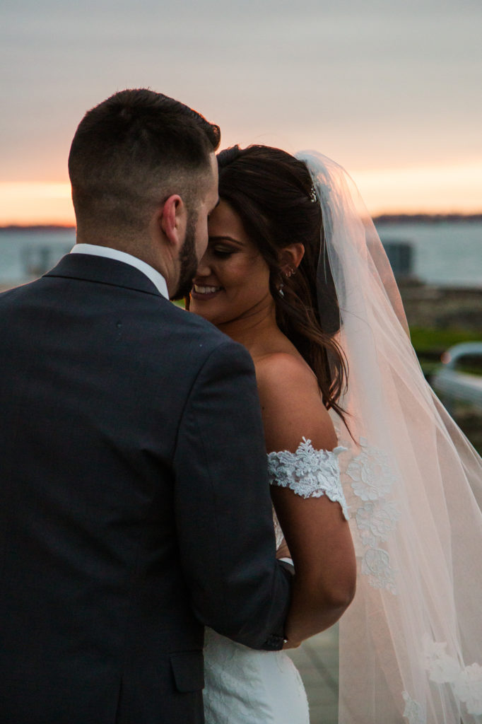Groom kisses bride's forehead at sunset during downtown Erie wedding