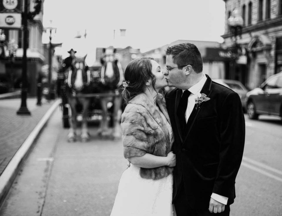 Bride and groom kiss with horse drawn carriage in the background