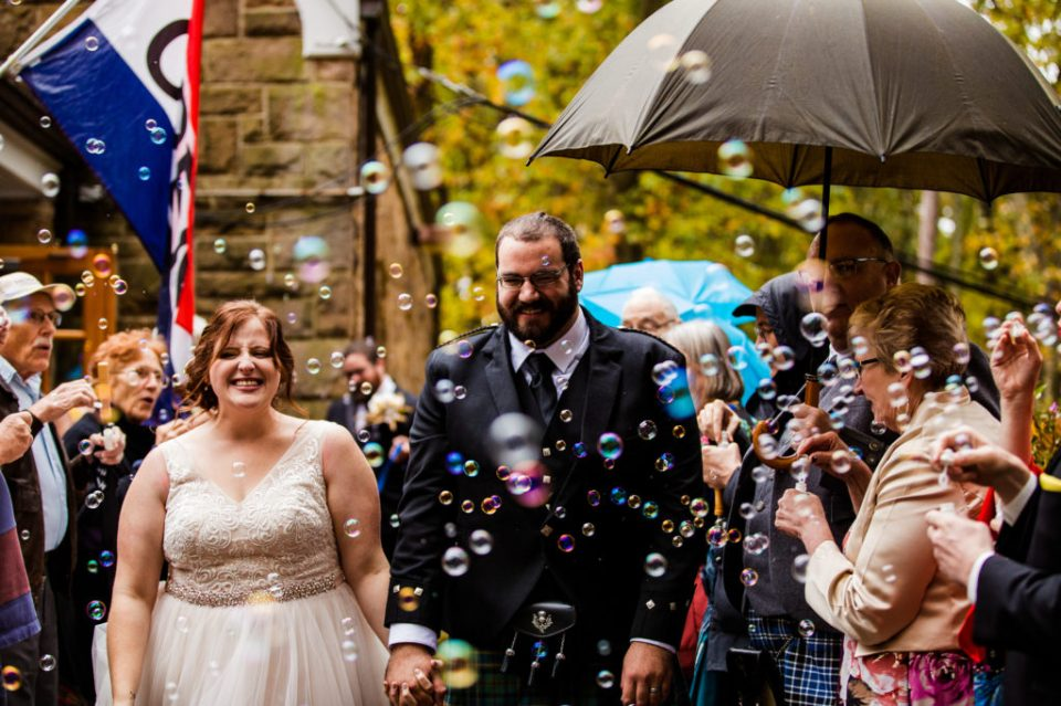 Bride and groom smiling during bubble exit after wedding at Bushy Run Battlefield