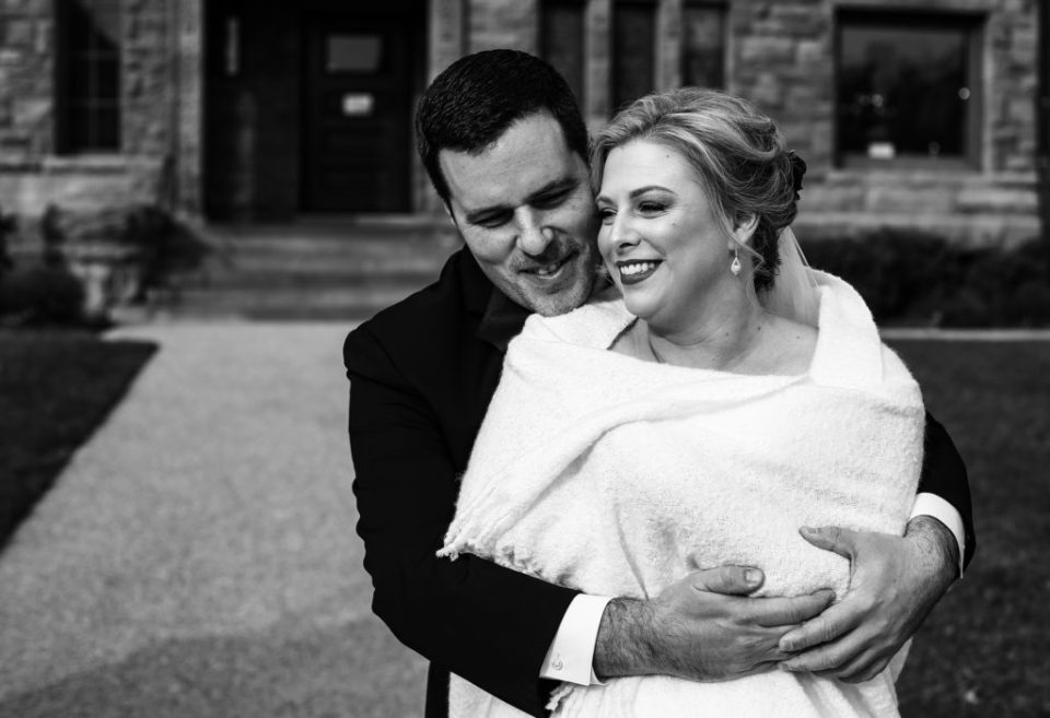 Groom embraces bride in front of Watson Curtze Mansion in Erie, PA