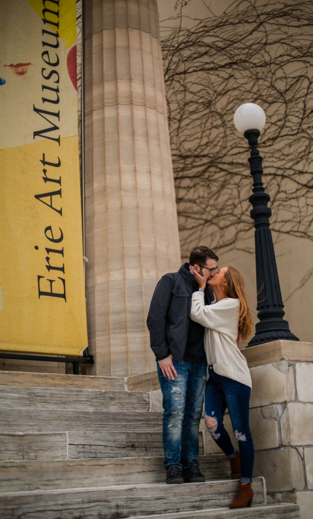 Engaged couple kissing on the steps of the Erie Art Museum in Erie, PA