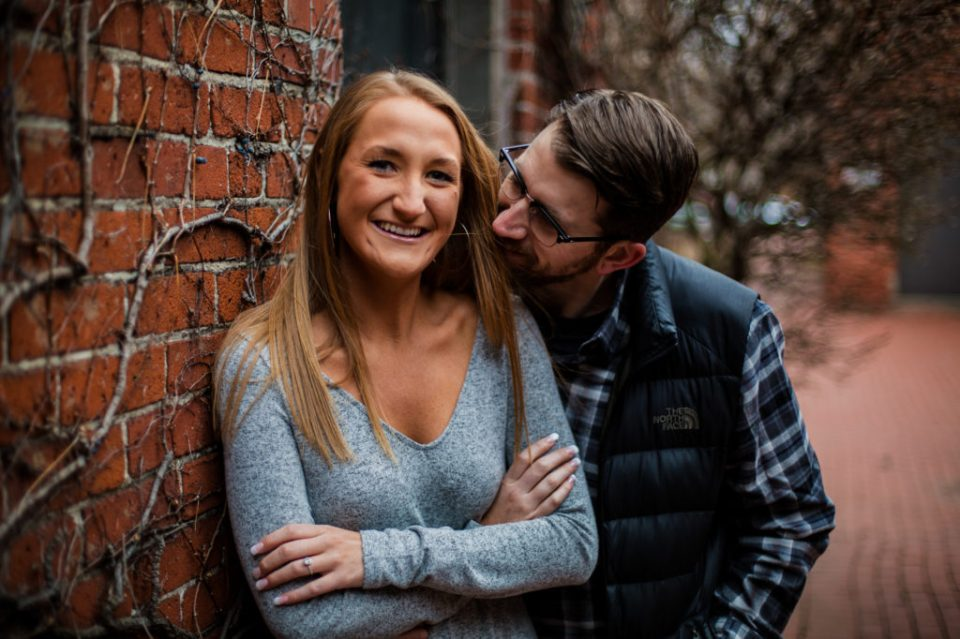 Woman looks at the camera while fiance smiles at her during engagement session at Modern Tool Square