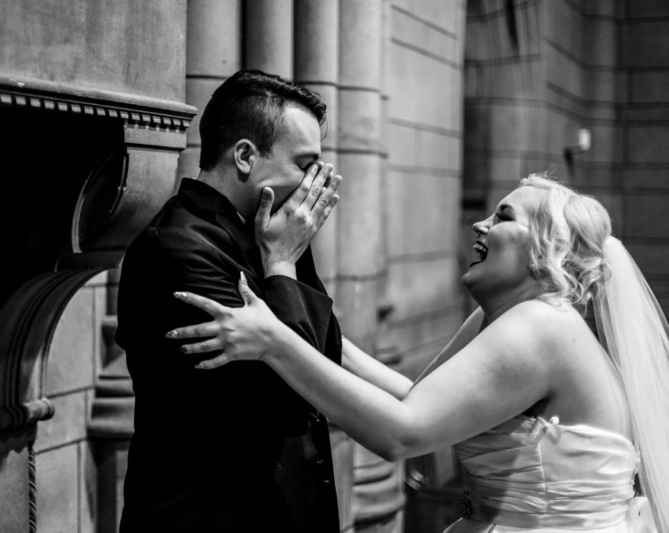 Groom reacts to seeing his bride for the first time on their wedding day during intimate first look portraits
