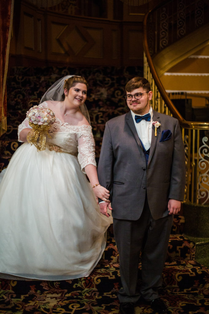 Bride grabs groom's arm to get his attention during first look photos in Erie, Pa's Warner Theatre