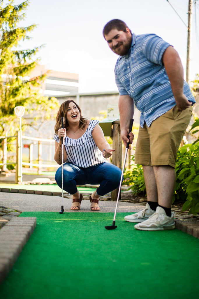 Couple plays mini golf at Harborview Miniature Golf Course during engagement photos in Erie, PA