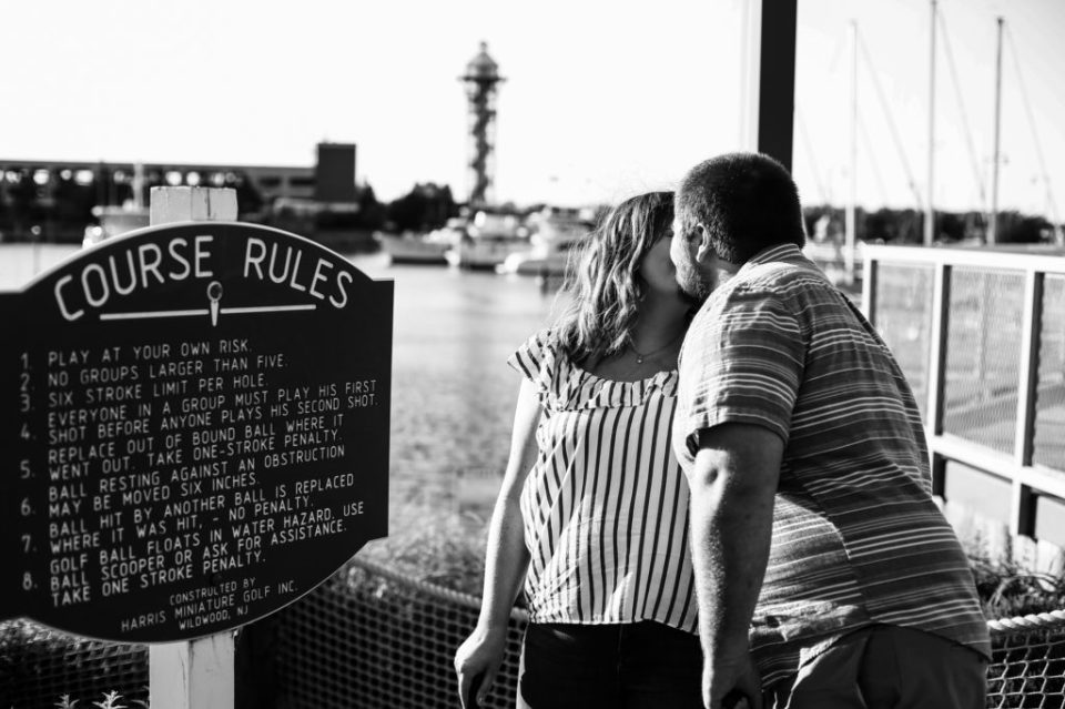 Couple kisses in front of sign at Harborview Miniature Golf Course in Erie PA