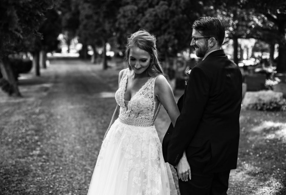 Groom smiles at his bride as they stroll together
