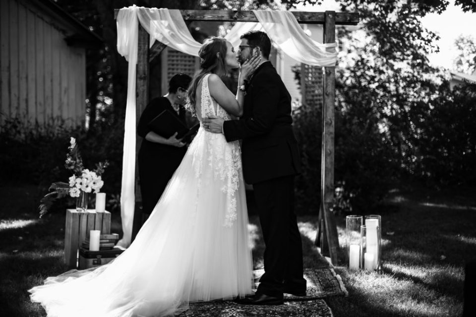 The first kiss at man and woman's intimate backyard wedding