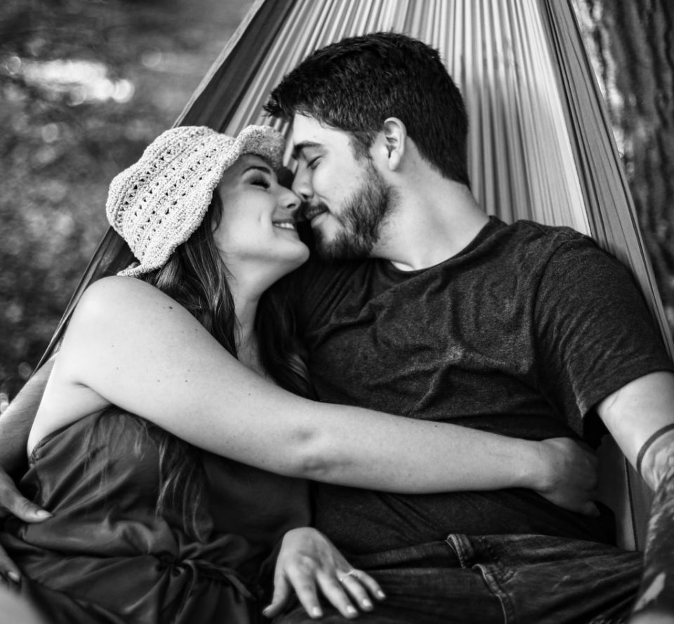 Couple snuggles in hammock for engagement photos at Wintergreen Gorge