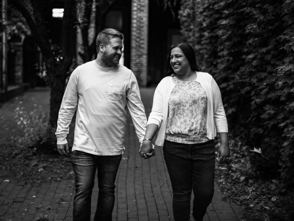 Engaged couple holding hands, smiling and walking through Modern Tool Square in Erie, PA