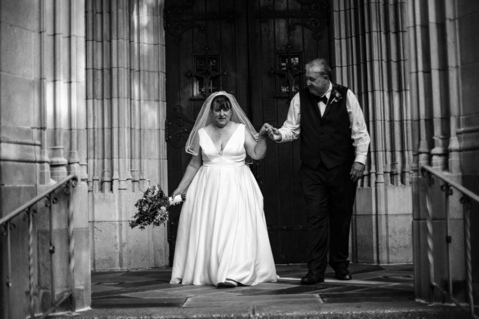 Bride and groom walk down steps of First Presbyterian Church of the Covenant in Erie, PA