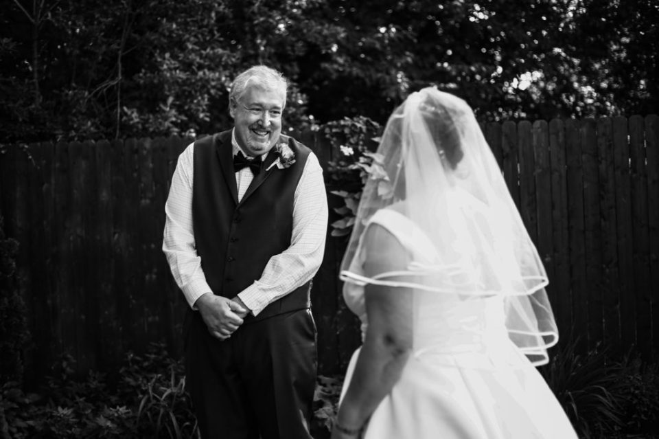 Groom smiles excitedly as he sees bride for the first time during first look portraits