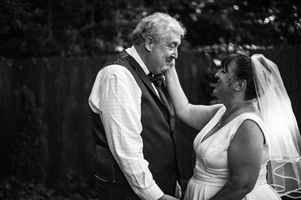 Bride touches groom's cheek during first look portraits before their intimate back garden wedding