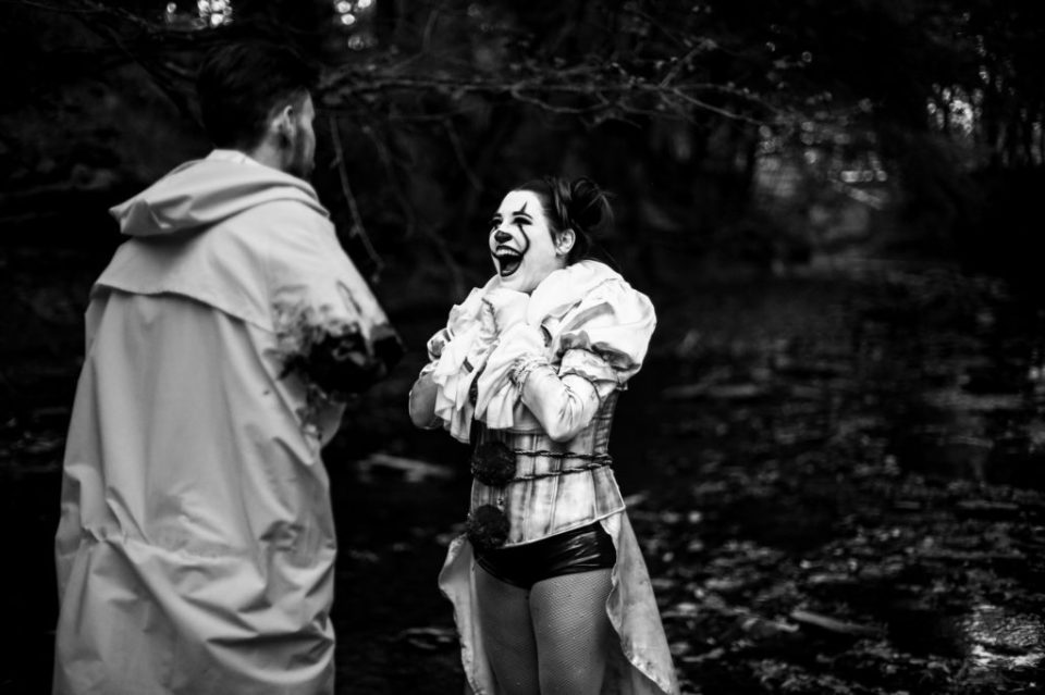 Woman in Pennywise costume laughing during Halloween engagement photo session