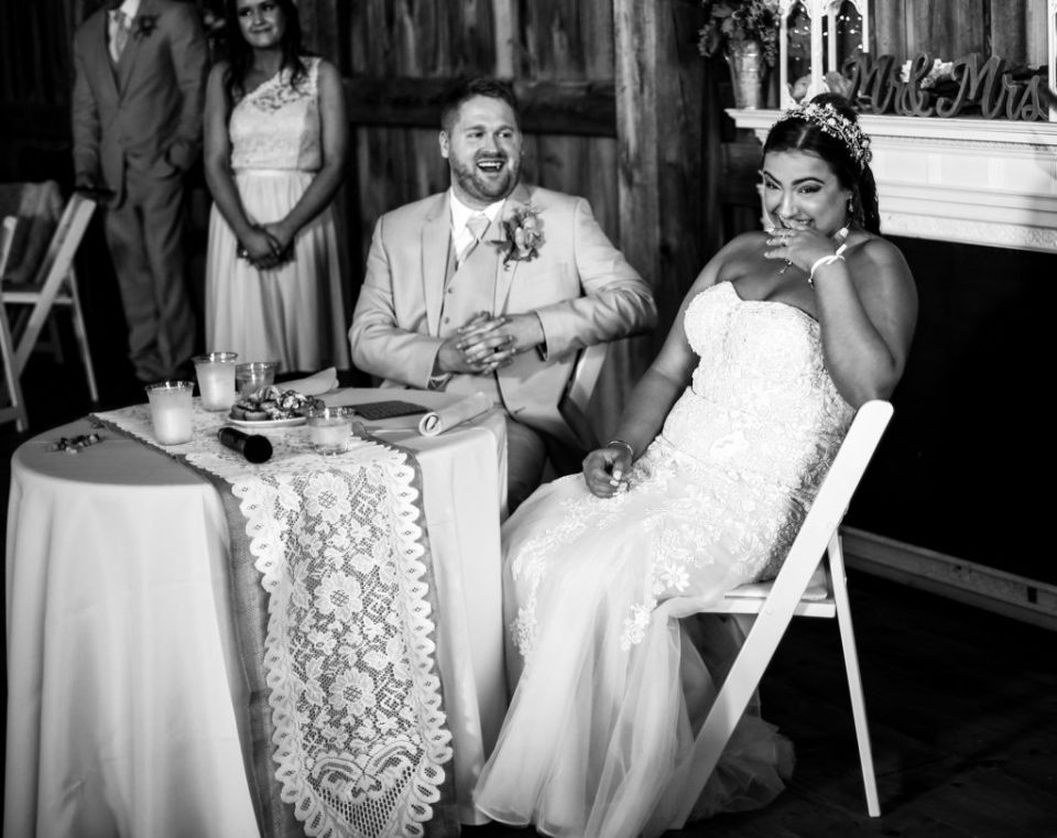 Bride and groom laughing during toasts at Port Farms reception